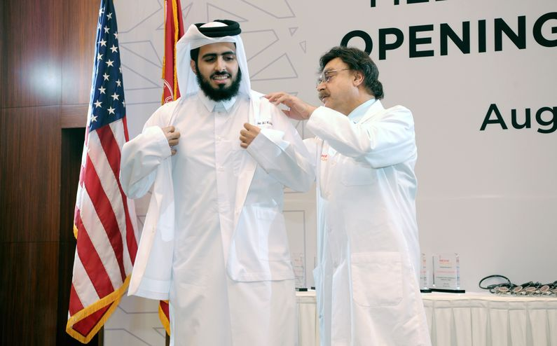 Nasser Al-Kuwari receiving his white coat from Dr. Javaid Sheikh.