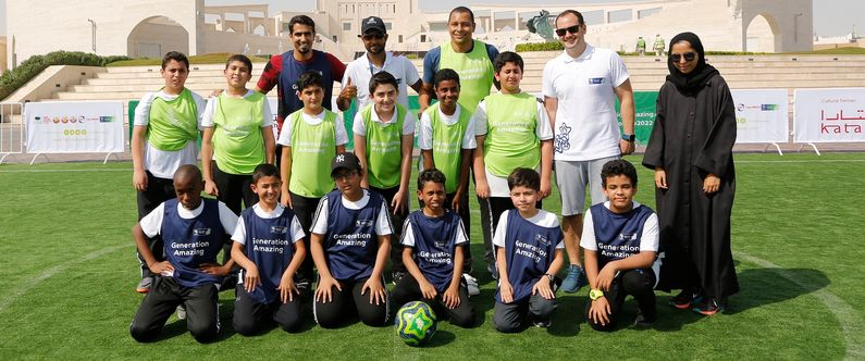 Mohammed Saadon Al Kuwari (left, back,) and Gilberto da Silva (3rd from left, back) with their young team mates and members of Generation Amazing.