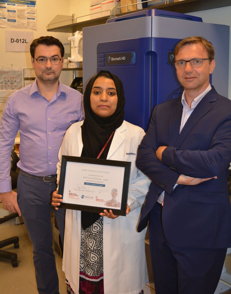 WCM-Q researchers Dr. Rudolf Engelke, left, Hina Sarwath and Dr. Frank Schmidt with the new Olink equipment and certificate.