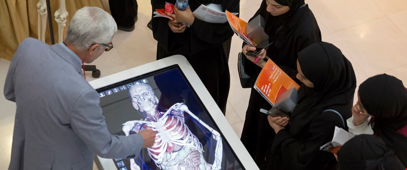 High school students at Medicine Unlimited inspect WCM-Q's hi-tech anatomage table.