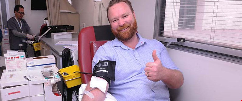 Nathan Heberley, WCM-Q's software development manager, donates to the blood drive.