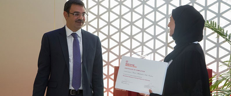 Dr. Khaled Machaca, Associate Dean for Research at WCM-Q, presents a certificate of graduation to one of the interns.