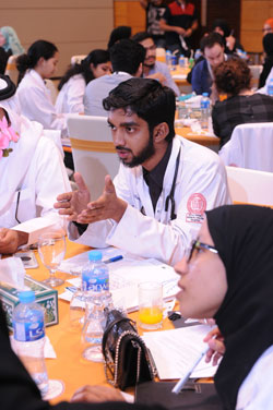 Med 3 student Adham Musthak discusses patient safety with fellow students.